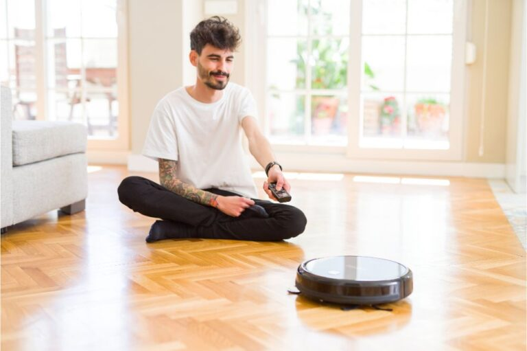 Young man using automatic vacuum cleaner to clean the floor